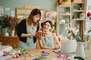 positive multiracial women working with tablet in floral store